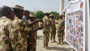 Des militaires nigérians devant un tableau affichant la liste des membres de Boko Haram les plu recherchés, à Maiduguri (Nigeria), le 21 novembre 2016. (AFP)