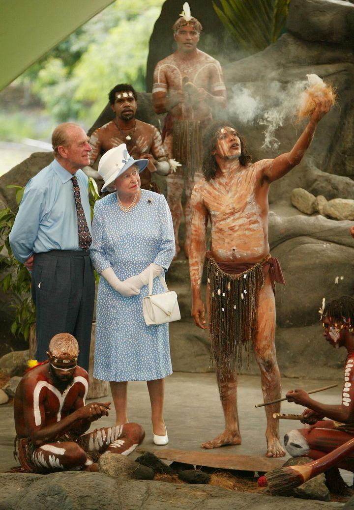 La reine Elizabeth II et le prince Philip observent des Aborigènes allumant un feu pour une cérémonie, à Cairns (Australie), le 1er janvier 2002. (TORSTEN BLACKWOOD / AFP)
