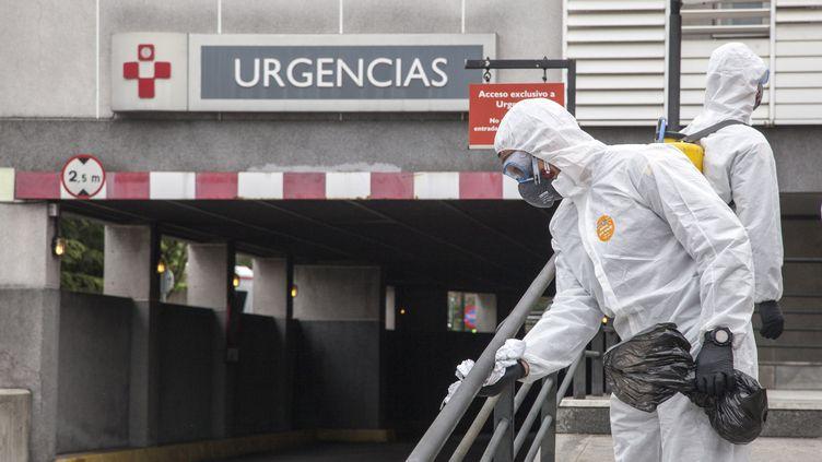 Des militaires espagnols désinfectent les escaliers devant les urgences d'un hôpital à Gijon, le 18 mars 2020. (ALVARO FUENTE / NURPHOTO / AFP)