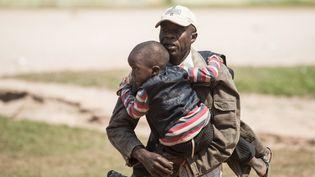 Un habitant de Bangui(Centrafrique) courant avec un enfant dans les bras, le 20 décembre 2013,au moment d'une fusillade. (FRED DUFOUR / AFP)