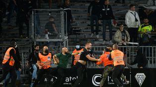 Les supporters de Marseille envahissent le terrain après le match de football de L1 française entre Angers (ASCO) et Marseille (OM), au stade Raymond-Kopa à Angers, le 22 septembre 2021. (JEAN-FRANCOIS MONIER / AFP)