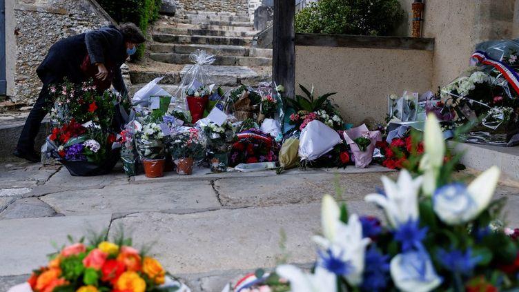 Une personne dépose des fleurs devant l'église de Saint-Léger-en-Yvelines (Yvelines), en hommage à Stéphanie Monfermé, le 29 avril 2021. (THOMAS SAMSON / AFP)