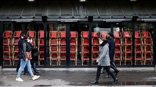 Des passants marchent devant un restaurant fermé à Paris, le 23 novembre 2020. (THOMAS COEX / AFP)