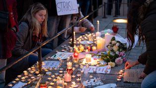 Des passants allument des bougies en hommage aux victimes de l'attentat de Strabourg, près du marché de Noël, le 12 décembre 2018. (SEBASTIAN GOLLNOW / DPA / AFP)
