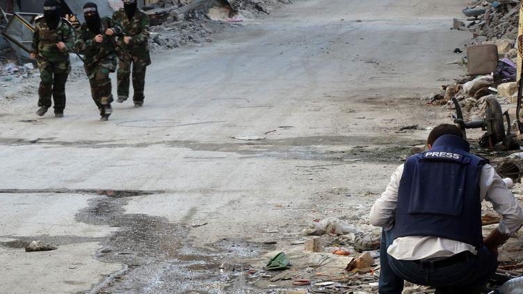 Trois rebelles masquées courent devant un journaliste dans la ville d'Alep en Syrie le 4 octobre 2013. AFP (MAHMUD AL-HALABI / MAHMUD AL-HALABI)