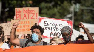 Des manifestants à Berlin (Allemagne) réclament l'accueil des demandeurs d'asile du camp grec de la Moria par les pays membres de l'Union européenne, le 20 septembre 2020. (STEFANIE LOOS / AFP)