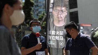 Le militant pro-démocratie Joshua Wong (à gauche), fait campagne le 11 juillet 2020 lors d'une élection primaire pour sélectionner les candidats de l'opposition pro-démocratie pour l'élection du conseil législatif de la ville en septembre, à Hong Kong. (MAY JAMES / MAY JAMES / AFP)