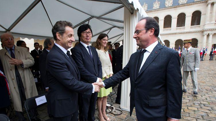 François Hollande et Nicolas Sarkozy se serrent la main lors de la cérémonie d'hommageaux harkis, le 25 septembre 2016, aux Invalides (Paris). (IAN LANGSDON / AFP)
