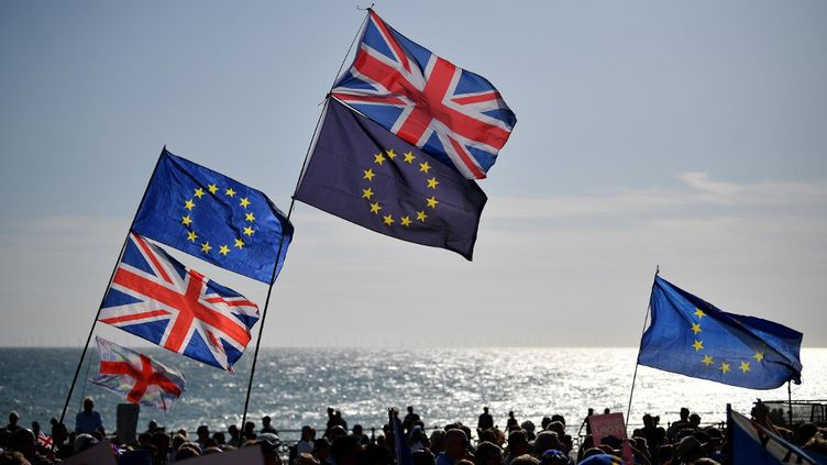 Les drapeaux britanniques et européens brandis lors d'une manifestation le 21 septembre 2019 à Brighton (Royaume-Uni). (DANIEL LEAL-OLIVAS / AFP)
