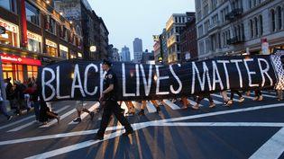 """Un policier passe devant une pancarte """"Black Lives Matter"""" le 9 juillet 2016 à New York. (KENA BETANCUR / AFP)"""