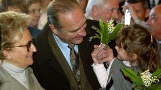Une enfant offre du muguet au président de la République et candidat à sa succession Jacques Chirac et à son épouse Bernadette, le 21 avril 2002 à la mairie de Sarran, à l'occasion du premier tour de l'élection présidentielle. (PATRICK KOVARIK / AFP)