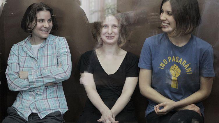 Les trois jeunes femmes du groupe punk russe Pussy Riot sourient à l'énoncé de leur jugement, le 17 août 2012 à Moscou (Russie). (ANDREY STENIN / RIA NOVOSTI / AFP)