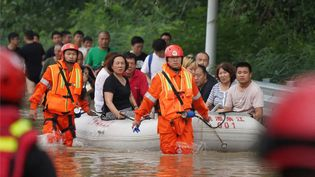 Les secouristes évacuent des habitants touchés par les inondations à Xingyang, dans la province du Henan (Chine), le 22 juillet 2021. (STRINGER / STRINGER / AFP)