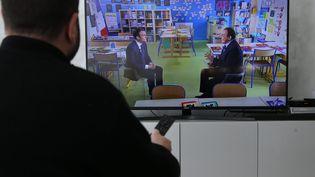 Un homme regarde le président de la République Emmanuel Macron invité du journal de 13 heures jeudi 12 avril 2018. (MAXPPP)