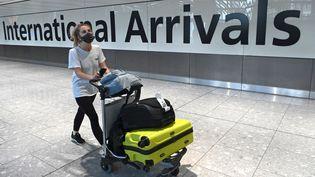 Une passagère arrive masquée à l'aéroport de Heathrow, à Londres (Grande-Bretagne) le 10 juillet 2020 (DANIEL LEAL-OLIVAS / AFP)