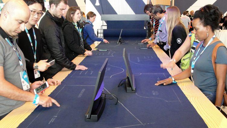 Des personnes testentun tissu sensible au toucher, permettant de commander des objets à distance grâce, développé par Google, à San Francisco, en Californie (Etats-Unis), le 29 mai 2015. (GLENN CHAPMAN / AFP)