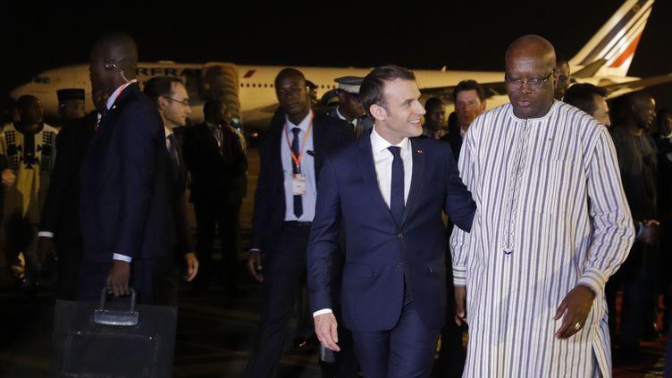 Le président français, Emmanuel Macron, est accueilli par le président du Burkina Faso, Roch Marc Christian Kaboré, à l'aéroport de Ouagadougou, le 27 novembre 2017. (PHILIPPE WOJAZER/POOL)
