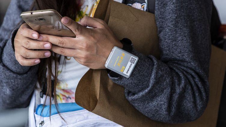 Une voyageuse porte un bracelet électronique, le 18 avril 2020 à Hong Kong. (ISAAC LAWRENCE / AFP)