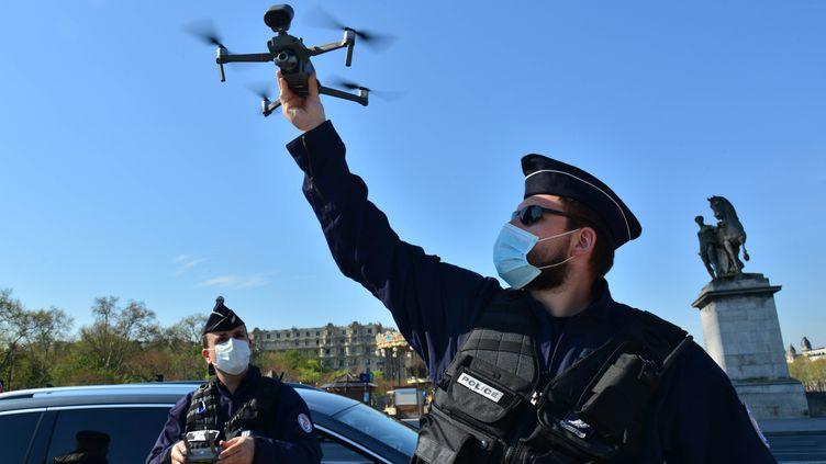 Des policiers déploient un drone au pied de la Tour Eiffel, à Paris, le 8 avril 2020. (ANTOINE LORGNIER / ONLY FRANCE / AFP)