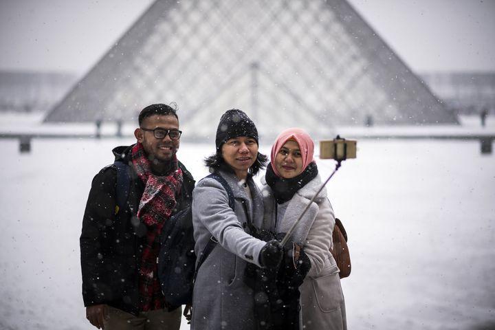 Des touristes se prennent en photo devant la pyramide du Louvre en février 2018.  (LIONEL BONAVENTURE / AFP)