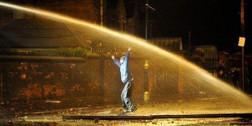 Jeune protestant défiant un canon à eau lors d'une émeute à Belfast le 12 juillet 2011. (AFP - STEPHEN WILSON )