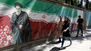 Des Iraniens passent devant une fresque représentant l'ayatollah Ruhollah Khomeini, à Téhéran, le 22 juin 2019. (ATTA KENARE / AFP)