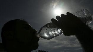 Boire 1,5L d'eau en cas de forte chaleur. (SEBASTIEN BOZON / AFP)
