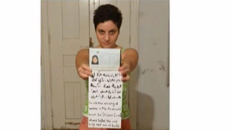 """La photo que Dana, une jeune égyptienne, a posté sur Facebook. Elle brandit son passeport dans lequel, elle apparaît voilée. En dessous, elle a écrit cette phrase: """"je soutiens le soulèvement des femmes du monde arabe parce que pendant vingt ans, je n'ai pas été autorisée à sentir le vent dans mes cheveux"""". ( FRANCE 2 / FRANCETV INFO)"""