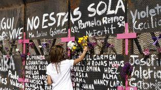 Une femme dépose des fleurs devant une fresque au Mexique où les noms de victimes ont été écrits, le 7 mars 2021. (EYEPIX / NURPHOTO)