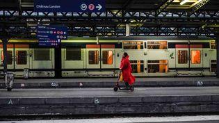 Une femme sur une trotinette sur un quai de la gare de l'Est le 13 décembre 2019 à Paris pendant la grève contre la réforme des transports. (MARTIN BUREAU / AFP)