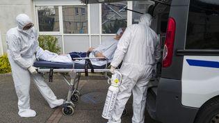 Des soignants transportent un malade du covid-19 aux urgences de l'hôpital Louis-Pasteur, à Colmar (Haut-Rhin), le 26 mars 2020. (SEBASTIEN BOZON / AFP)