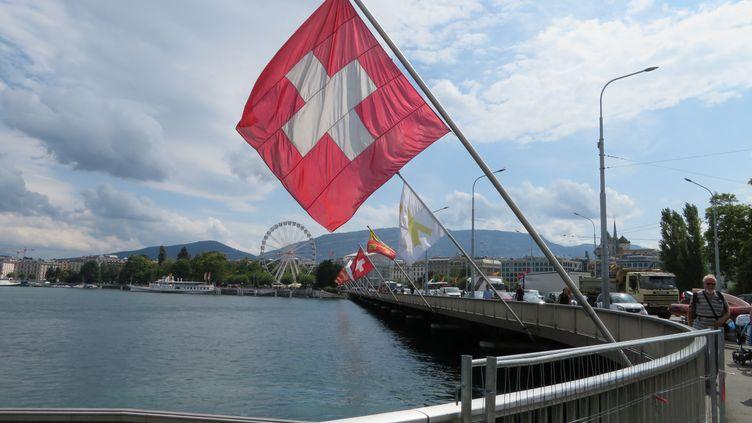 Vue sur le bord du lac Léman à Genève en Suisse, avec un drapeau suisse au premier plan, fin août 2018. (STÉPHANE MILHOMME / FRANCE-INFO)