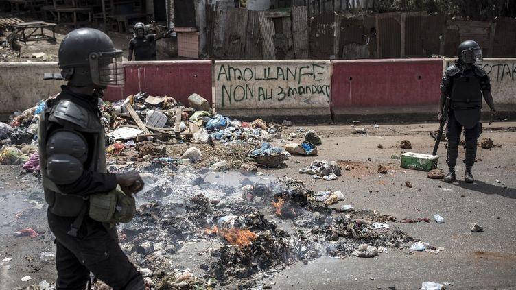 """Des policiers postés sur """"l'Axe de la démocratie"""", épicentre de la contestation contre le régime du président Alpha Condé, alors que des manifestations ont de nouveau éclaté le 29 février 2020 dans la banlieue de Conakry (la capitale de la Guinée) après l'annonce d'un report du référendum constitutionnel qui devait se tenir le 1er mars. (JOHN WESSELS / AFP)"""