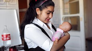 Leonarda Dibrani, 15 ans, porte une poupée dans ses bras, dans une maison de Mitrovica (Kosovo), le 19 octobre 2013, après son expulsion de France. (ARMEND NIMANI / AFP)