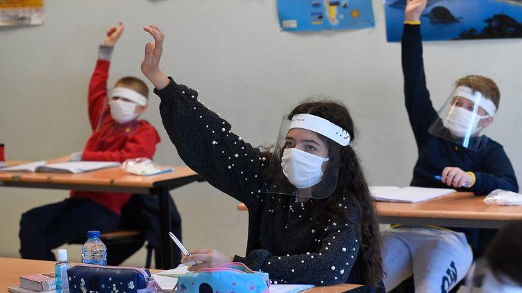 Des élèves masqués pour éviter d'être contaminé par le coronavirus, le 18 mai 2020 à Saint-Grégoire (Ille-et-Vilaine). (DAMIEN MEYER / AFP)