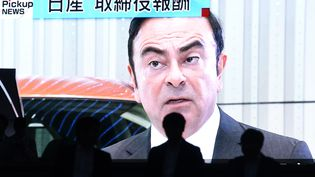 Des gens passent devant un écran géant qui diffuse des images de Carlos Ghosn, patron de Renault-Nissan-Mitsubishi, à Tokto (Japon), le 20 novembre 2018.  (TOSHIFUMI KITAMURA / AFP)