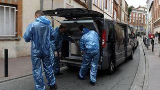 Des spécialistes de l'identité judiciaire emportent dans leur véhicule le corps de l'étudiante retrouvée morte à Toulouse, le 4 août 2015. (STRINGER / AFP)