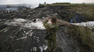 (Un séparatiste pro-russe prend des photos du site du crash. © Maxim Zmeyev/Reuters)