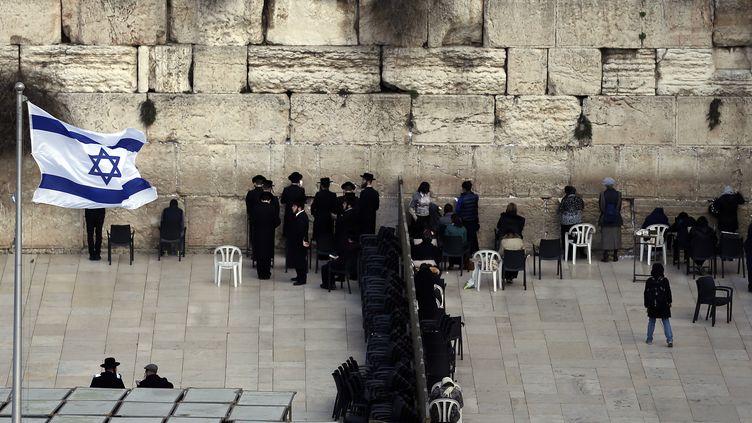 Des juifs ultra-orthodoxes (à g.) et des femmes prient dans deux sections différentes du Mur occidental, le site le plus sacré où les Juifs peuvent prier, dans la vieille ville de Jérusalem, le 2 février 2016. (THOMAS COEX / AFP)