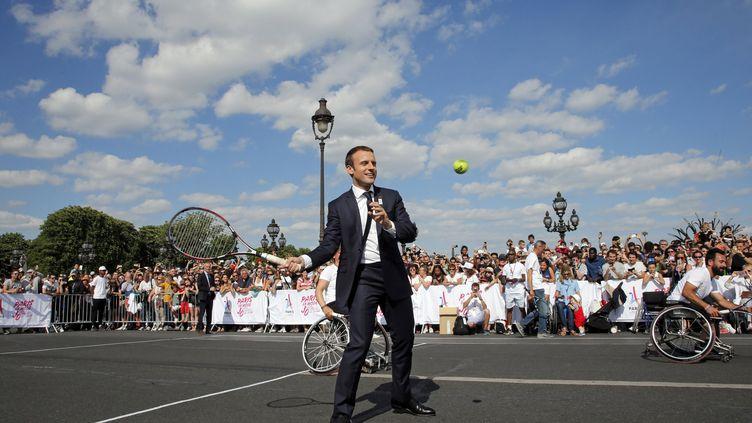 Emmanuel Macron joue au tennis sur le pont Alexandre III à Paris, le 24 juin 2017, pour soutenir la candidature de la capitale comme ville organisatrice des Jeux olympiques et paralympiques 2024. (JEAN-PAUL PELISSIER / POOL / REUTERS POOL)