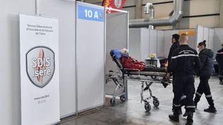 Des pompiers déplacent un homme âgé auvaccinodrome d'Alpexpo, à Grenoble (Isère), le 9 avril 2021. (PHILIPPE DESMAZES / AFP)