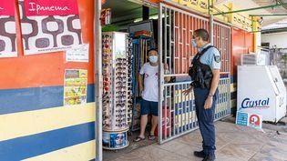 Un gendarme contrôle un commerçant àRemire-Montjoly, le 20 juin 2020, dans la banlieue de Cayenne (Guyane). (JODY AMIET / AFP)