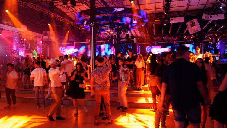 """Des personnes dansent dans la boîte de nuit """"La Dune"""" à La Grande Motte,(Hérault), le 10 juillet 2021. (SYLVAIN THOMAS / AFP)"""