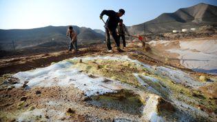 Des ouvriers nettoient un sol pollué, dans la province de Gansu (nord-ouest de la Chine), en octobre 2011. (NIE JIANJIANG / XINHUA / AFP)
