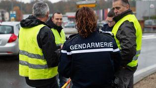 """Une gendarme en compagnie de """"gilets jaunes"""", le 17 novembre 2018 à Pont-de-Beauvoisin (Savoie). (ROMAIN LAFABREGUE / AFP)"""
