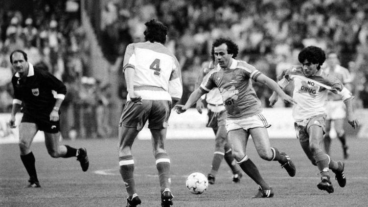 Diego Maradona à la poursuite de Michel Platini sur la pelouse du stade Marcel-Picot à Nancy (Meurthe-et-Moselle) à l'occasion du jubilé du joueur français le 24 mai 1988. (ERIC FEFERBERG / AFP)