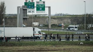 Un poids lourd entouré de migrants, le 3 décembre 2015, autour de Calais (Pas-de-Calais). (PHILIPPE HUGUEN / AFP)