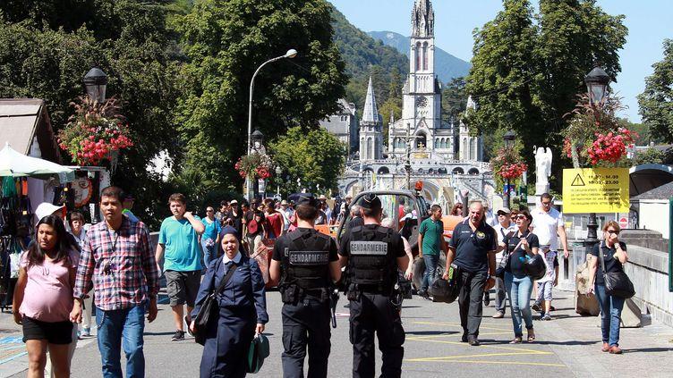 Des officiers de police patrouillent aux abords du sanctuaire de Lourdes (Hautes-Pyrénées), lors du pélérinage de l'assomption, le 14 août 2016. (BOB EDME / AP / SIPA)