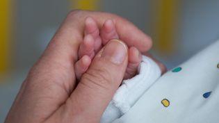 Une femme tient la main de son fils dans une maternité de Dortmund (Allemagne), le 5 août 2015. (MARCEL KUSCH / DPA / AFP)