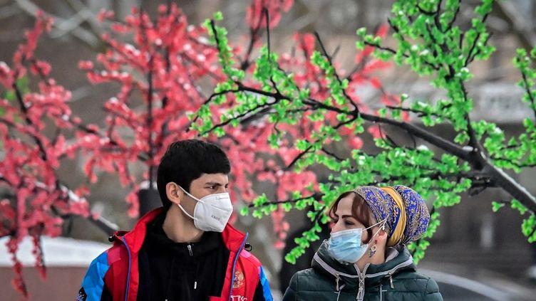 Un homme et une femme portant un masque et se promenant dans la ville de Chekhov, à 70 km de Moscou, en Russie, le 21 décembre 2020. (YURI KADOBNOV / AFP)
